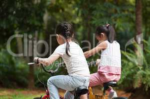 Active Asian children riding bicycle outdoor.