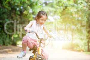Active Asian child riding bike outdoor.