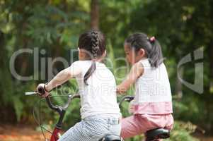 Active Asian children riding bike outdoor.