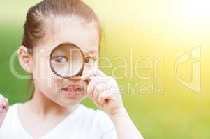 Asian kid with magnifier glass at outdoors.