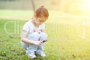 Child exploring nature with magnifier glass at outdoors.