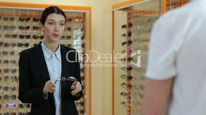 Charming optician selling glasses in optical shop