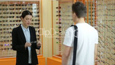 Female optician showing glasses to man at optics