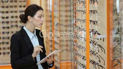 Attractive optician working with tablet in optics