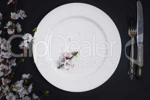 Empty white plate with cutlery on a black wooden surface