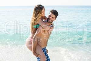 Boyfriend piggybacking girlfriend on shore at beach