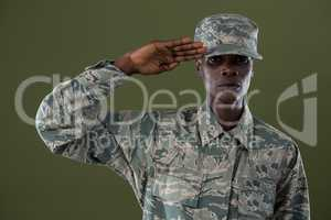 Androgynous man in camouflage uniform saluting