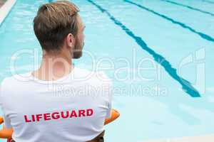 Lifeguard sitting on chair with rescue buoy at poolside