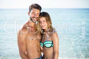 Young couple standing with arm around on shore at beach
