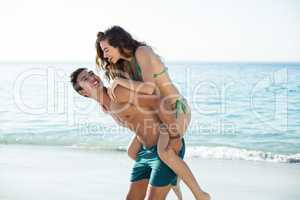 Boyfriend piggybacking girlfriend on shore