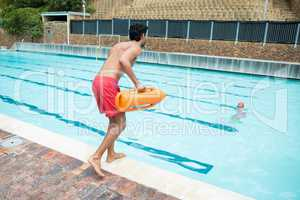 Lifeguard jumping into a swimming pool to rescue drowning boy