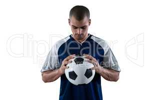 Football player holding football with both hands