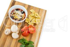 Food in bowl by ravioli and vegetables on cutting board