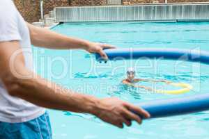 Trainer demonstrating use of pool noodle