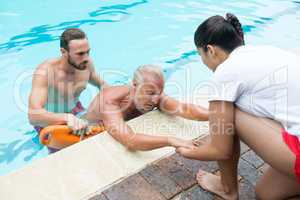 Lifeguards rescuing senior man from swimming pool
