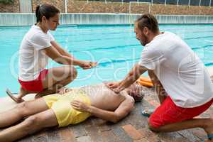 Lifeguards pressing chest of unconscious senior man