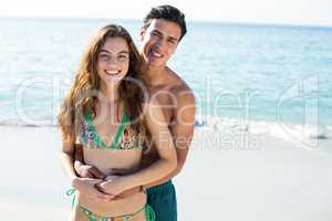 Happy man embracing girlfriend standing on shore at beach