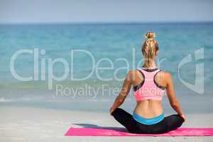 Rear view of woman meditating while sitting on shore