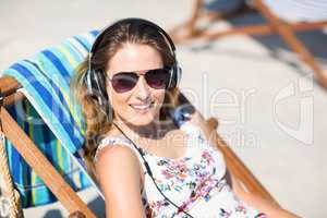 Young woman listening songs while relaxing on deck chair