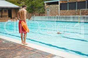 Lifeguard jumping into a swimming pool to rescue drowning senior man