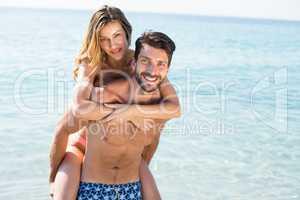 Happy man piggybacking girlfriend on shore at beach