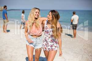 Friends with arm around walking on shore at beach