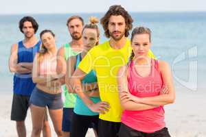 Friends in sports clothing standing at beach