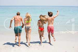 Couples in beachwear running on shore