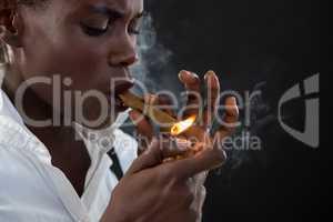 Androgynous man lighting a cigar