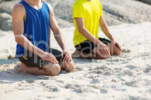 Friends in sports clothing kneeling on shore at beach