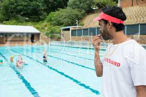 Lifeguard blowing whistle while students playing in pool