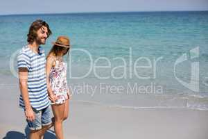 Couple walking on seashore during sunny day