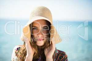 Portrait of young woman wearing hat while standing at beach