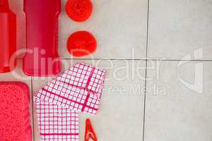 Overhead view of red cleaning products with napkin