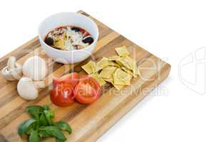 Cooked food in bowl by ravioli and vegetables on cutting board