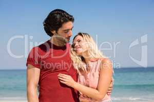 Couple with arm around standing on shore at beach