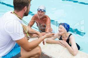 Swim coach showing stop watch to senior couple