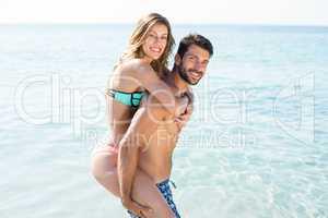 Young man piggybacking girlfriend on shore at beach