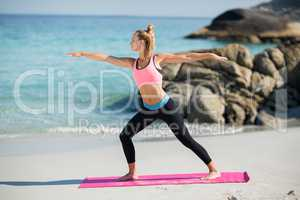 Young woman practicing warrior pose at beach