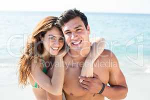 Happy young couple standing on shore at beach