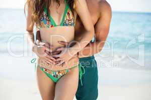 Man embracing girlfriend standing on shore