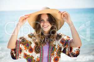 Happy young woman wearing hat while standing at beach