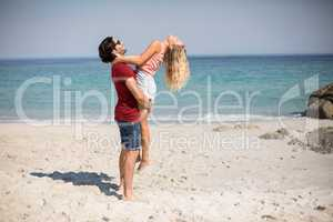 Boyfriend carrying girlfriend while standing at beach