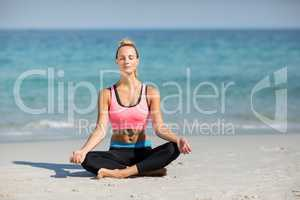Woman meditating in lotus position at beach