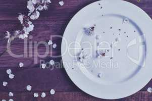 White empty plate on a brown wooden surface