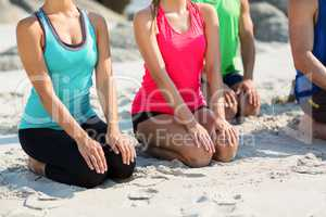 Friends in sports clothing kneeling on shore