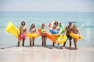 Friends with inflatable rings and pool rafts on seashore