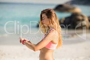 Woman looking at wristwatch while standing on shore