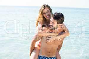 Man piggybacking girlfriend on shore at beach