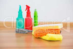 Cleaning sponge and chemical bottles on hardwoodfloor